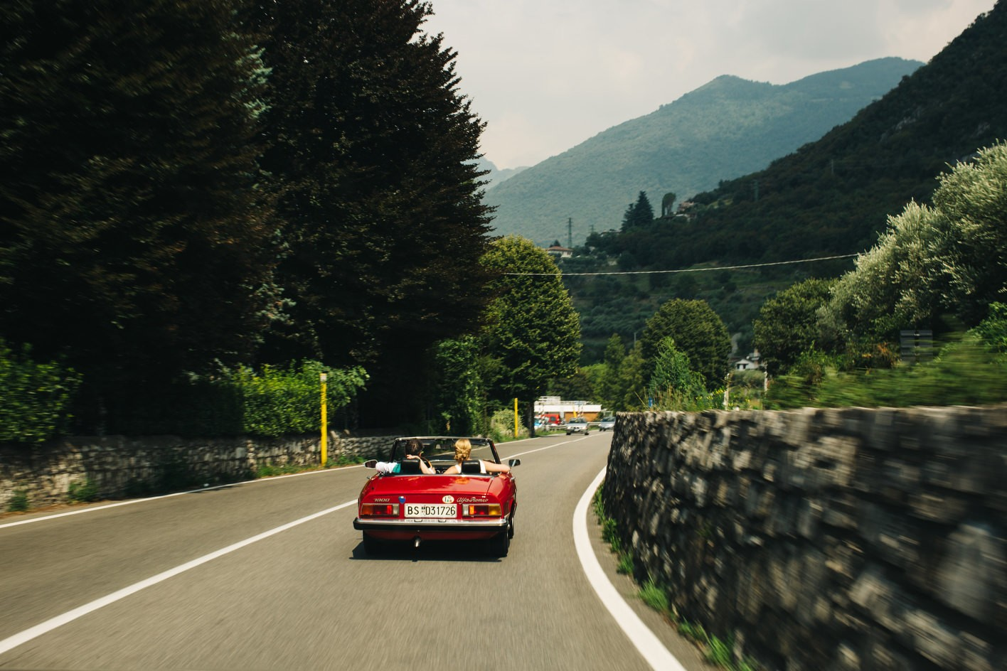 Bride and groom drive around italian hills to lake iseo