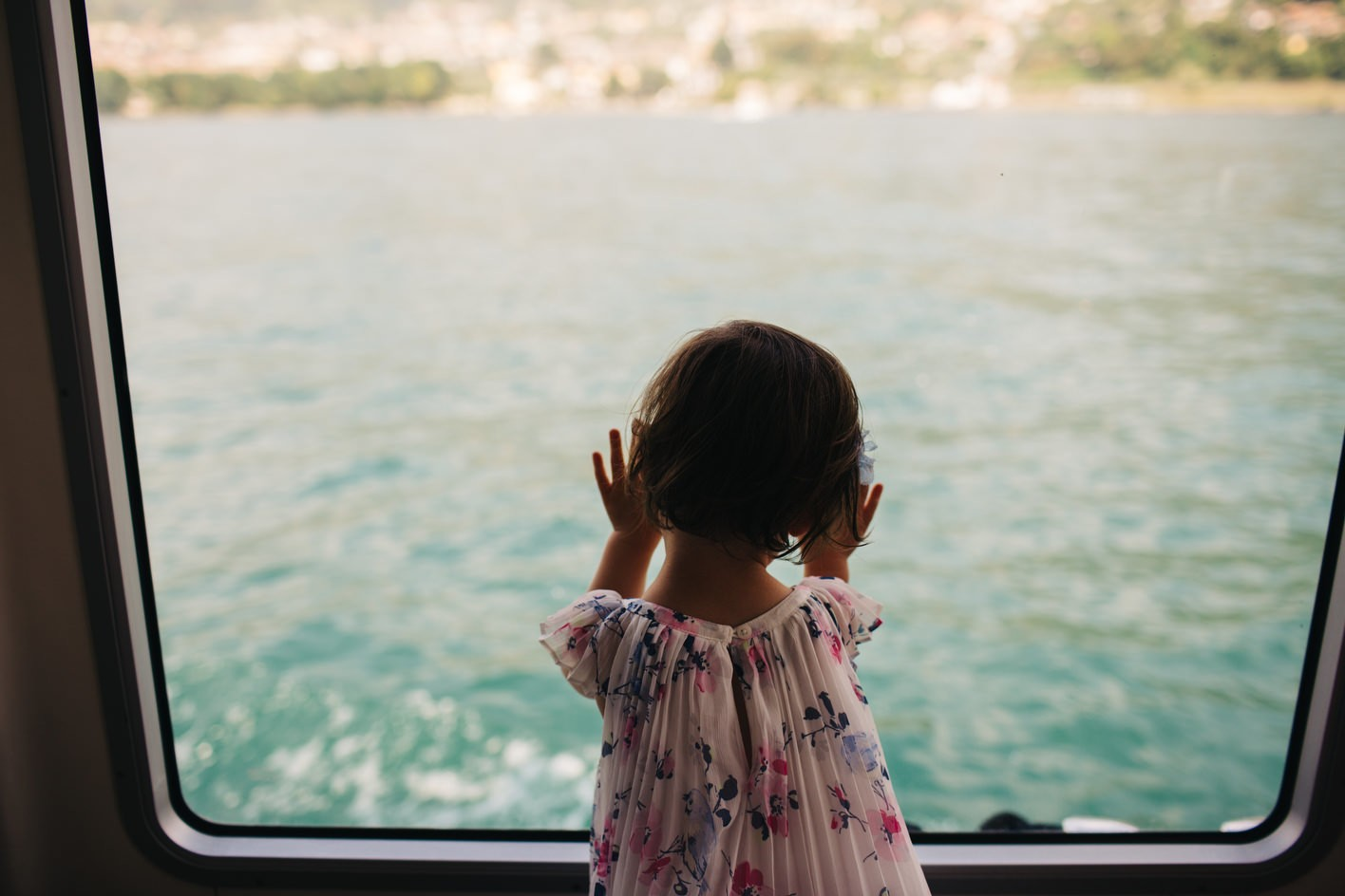 little girl looks out of window of boat