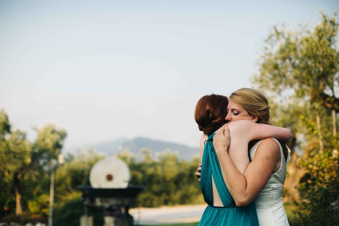 brides and maid of honor hug after speech