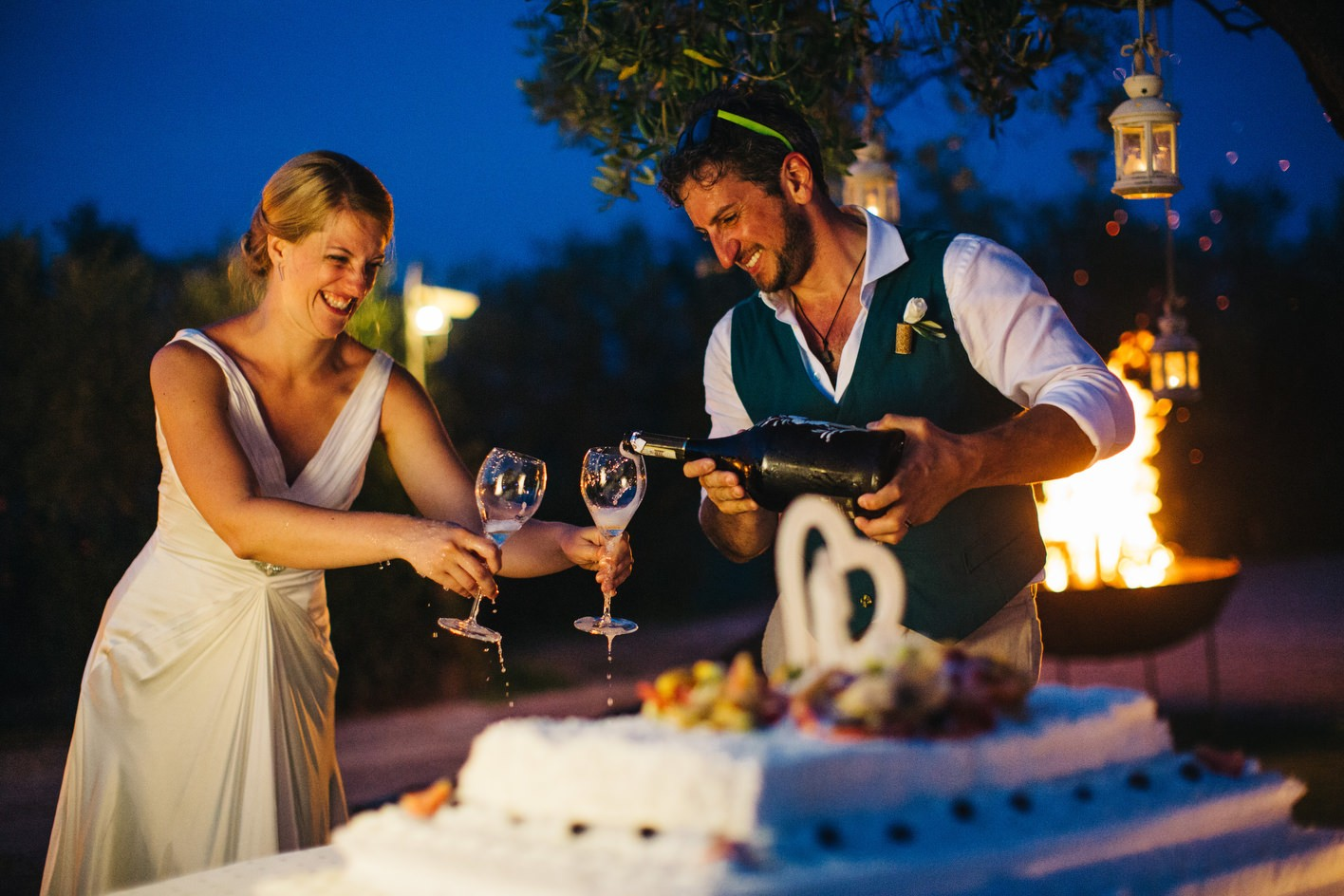 bride and groom cut cake and enjoy wine