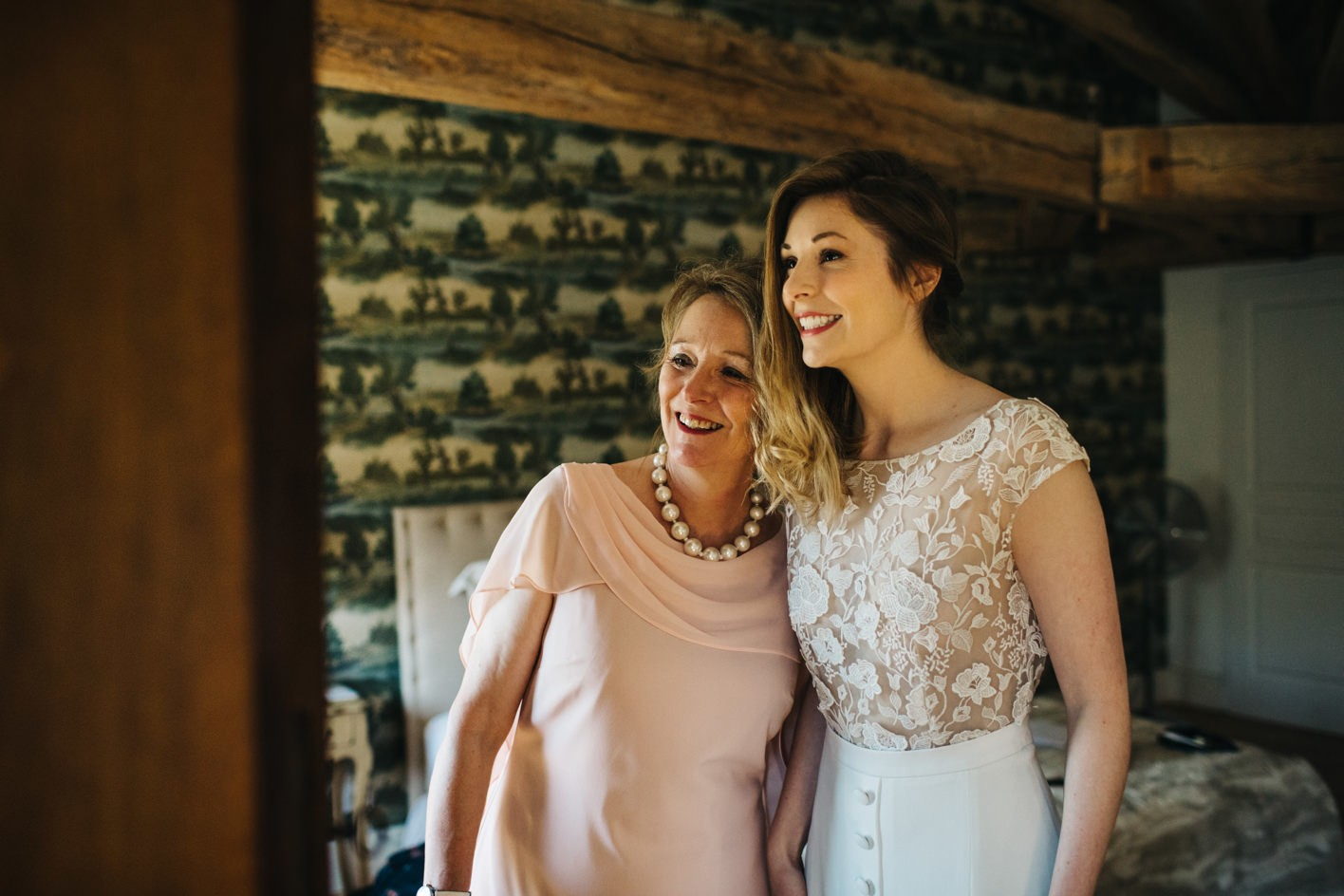 bride and mother smile in mirror
