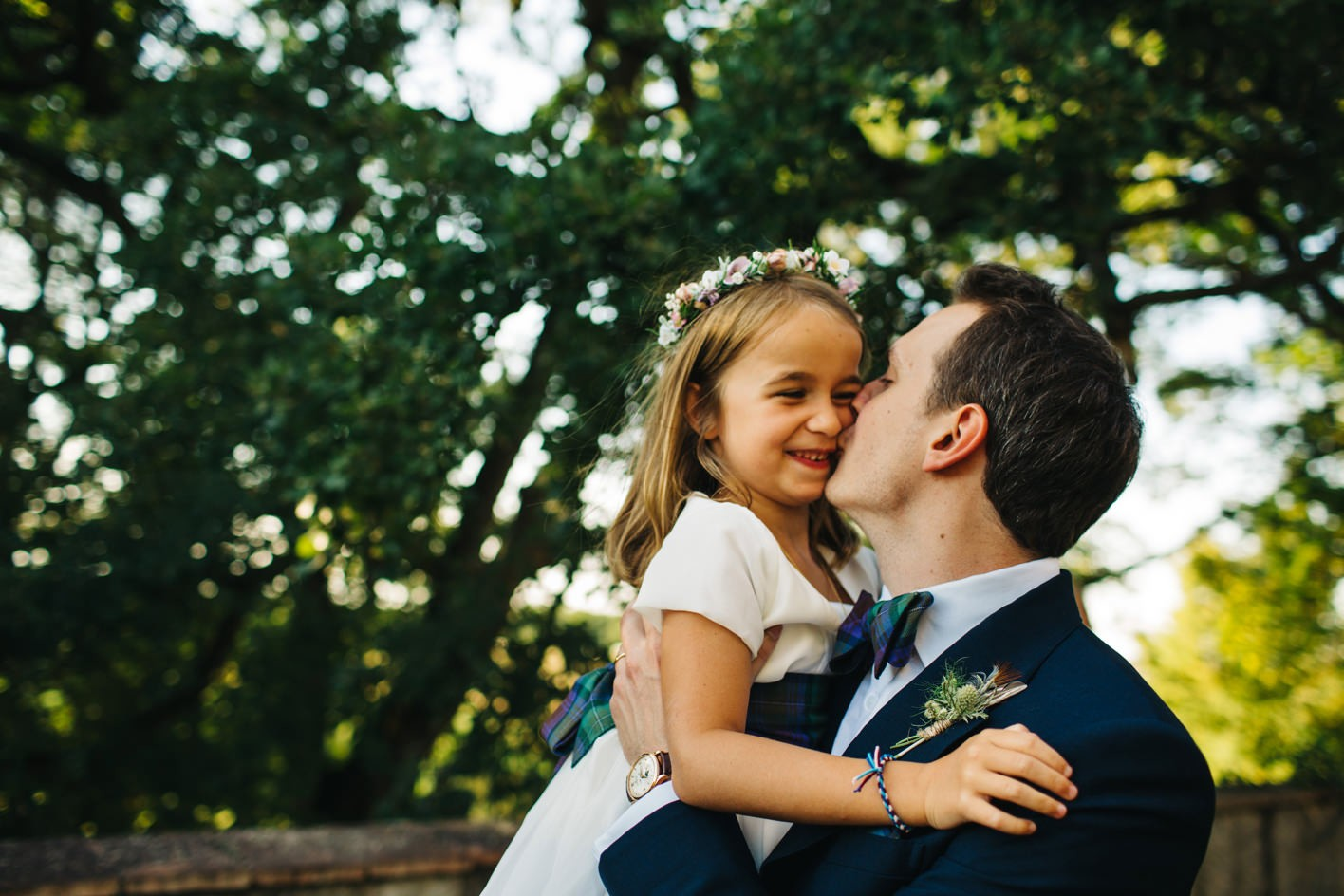 groom kisses flower girl