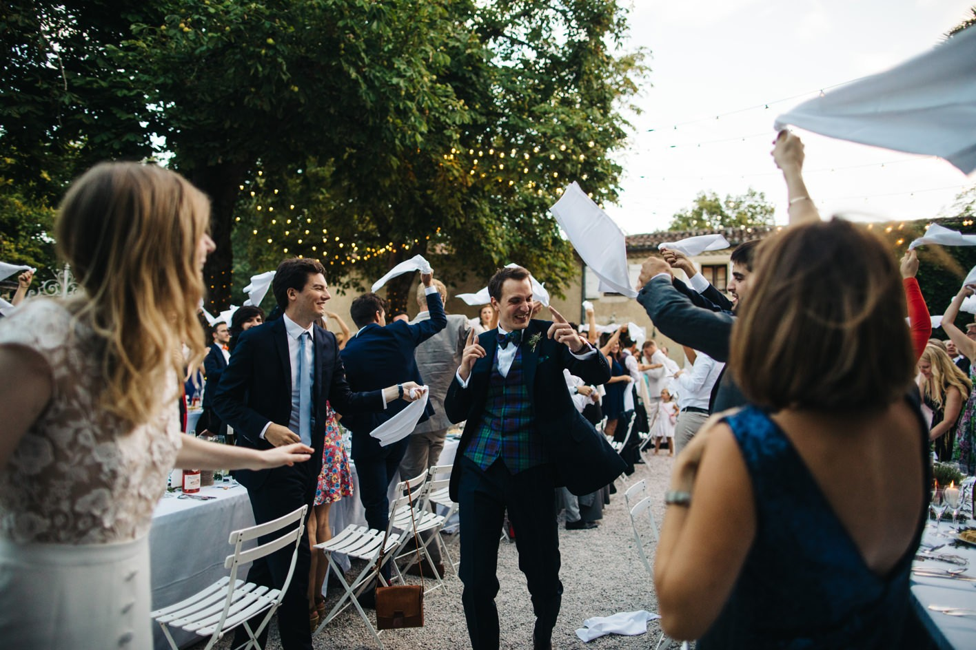 groom making an entrance at courtyard wedding reception