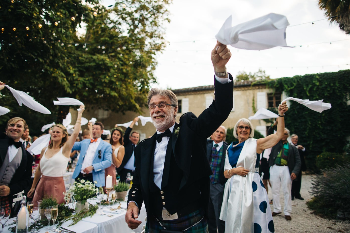 guests wave serviette at french wedding