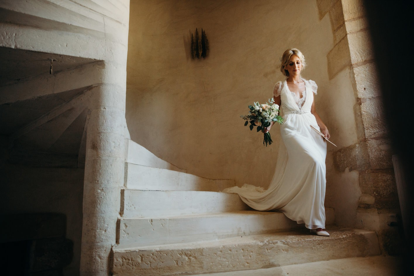 bride walking down stairs at chateau de la bourlie