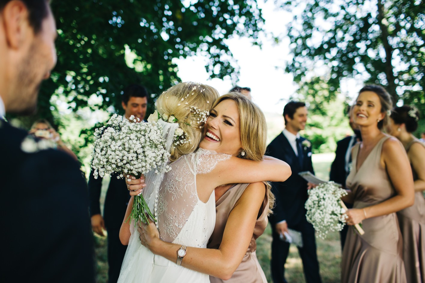 bridesmaid hugs bride