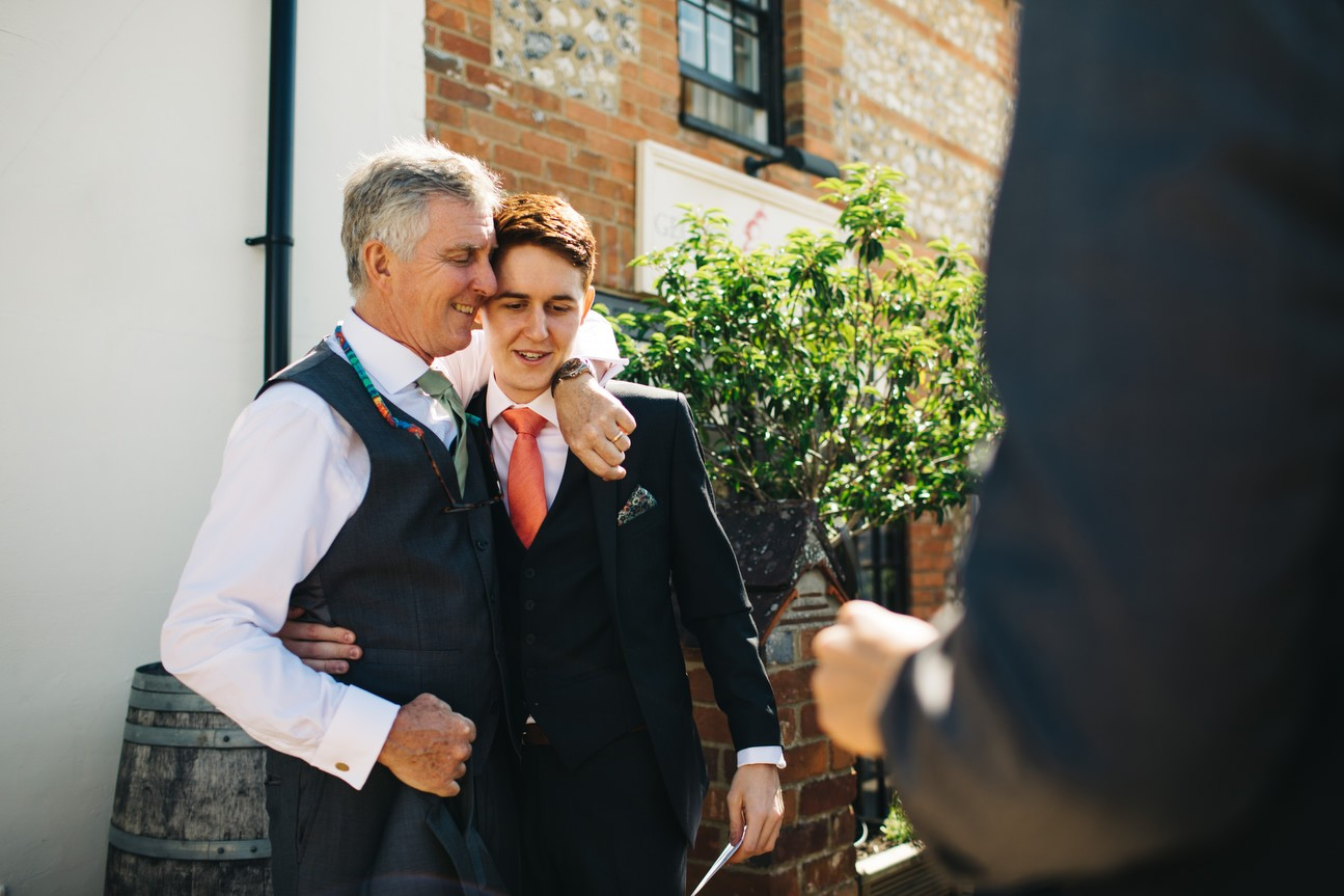 father of groom hugs son