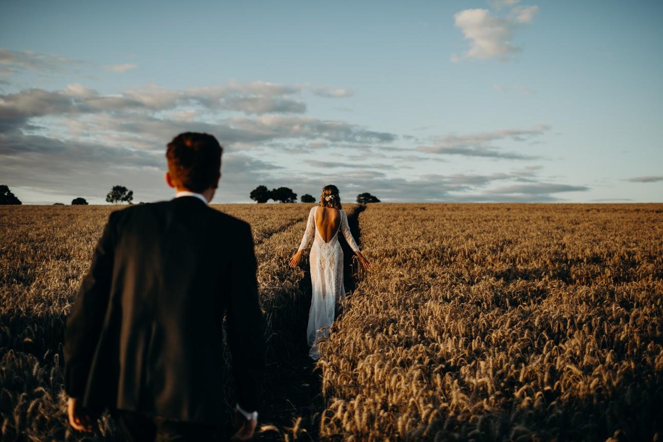 bride walks in distance as groom folllows