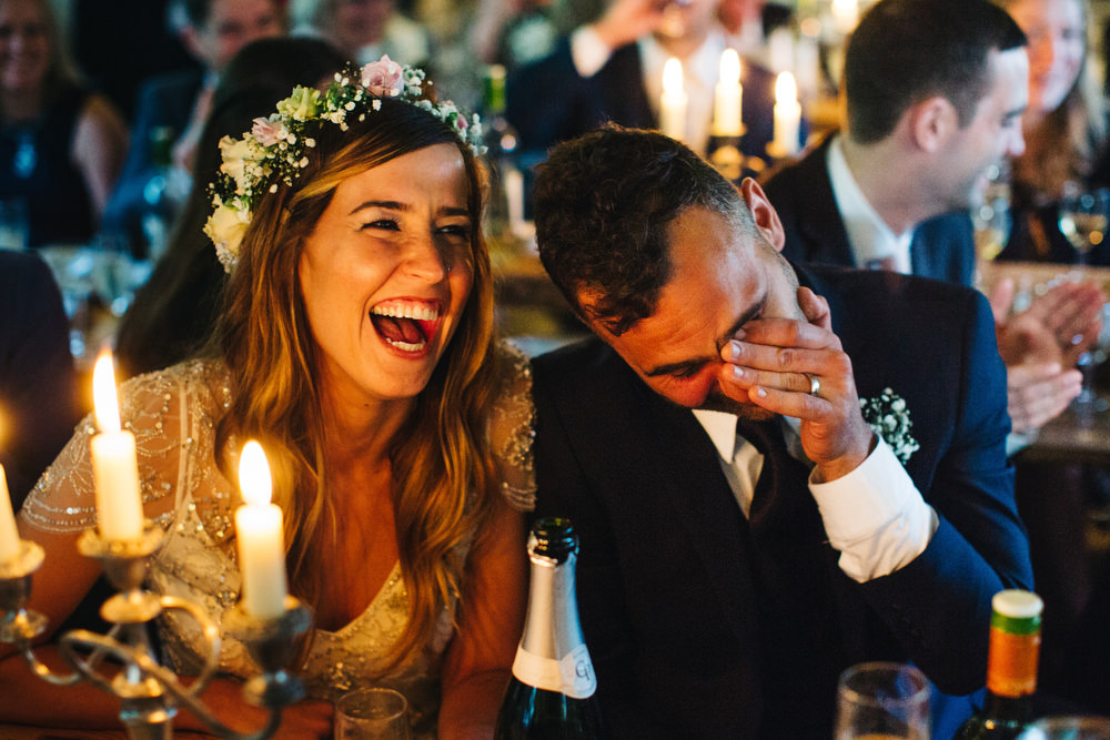 unposed photograph of Couple laugh during speeches
