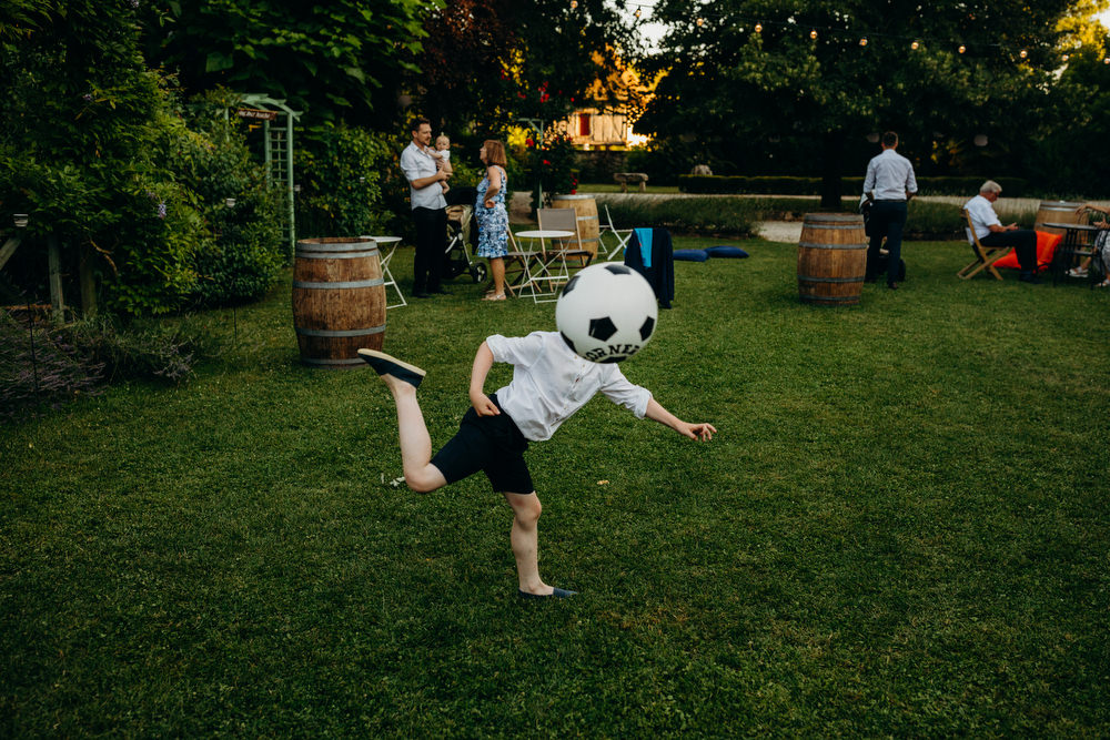 Boy plays with football at wedding