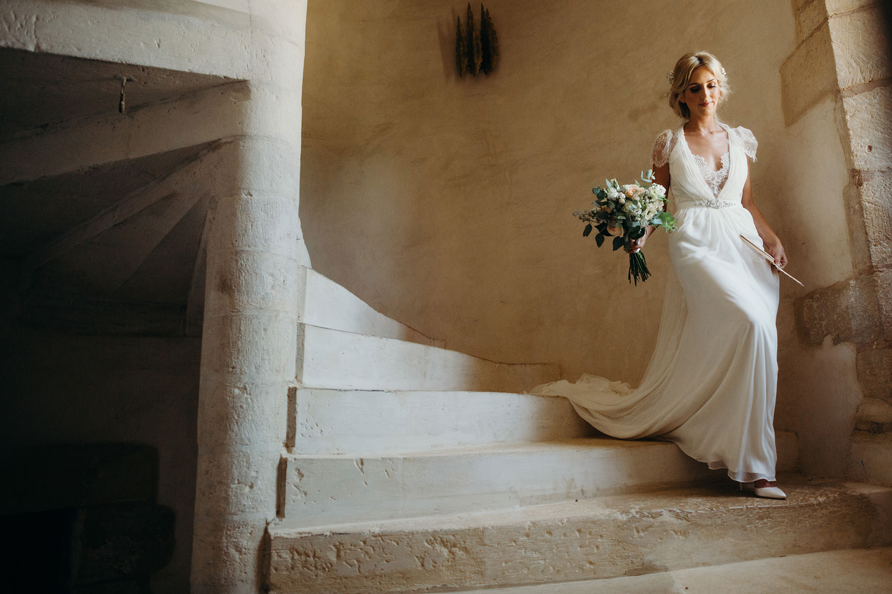 Bride walks down stairs at Chateau destination wedding