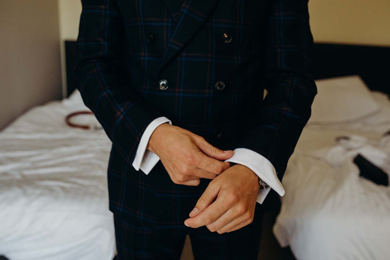 Groom putting suit on