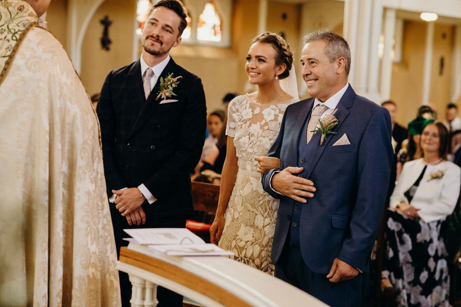 Bride, father and groom smile at altar