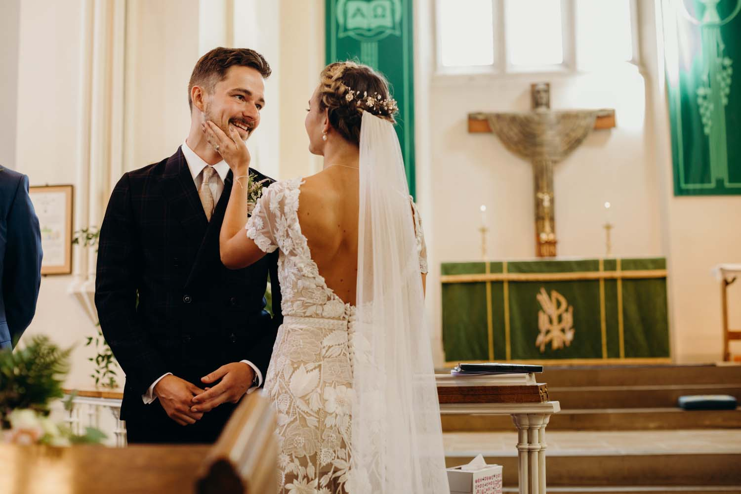 Bride puts hand on smiling grooms face
