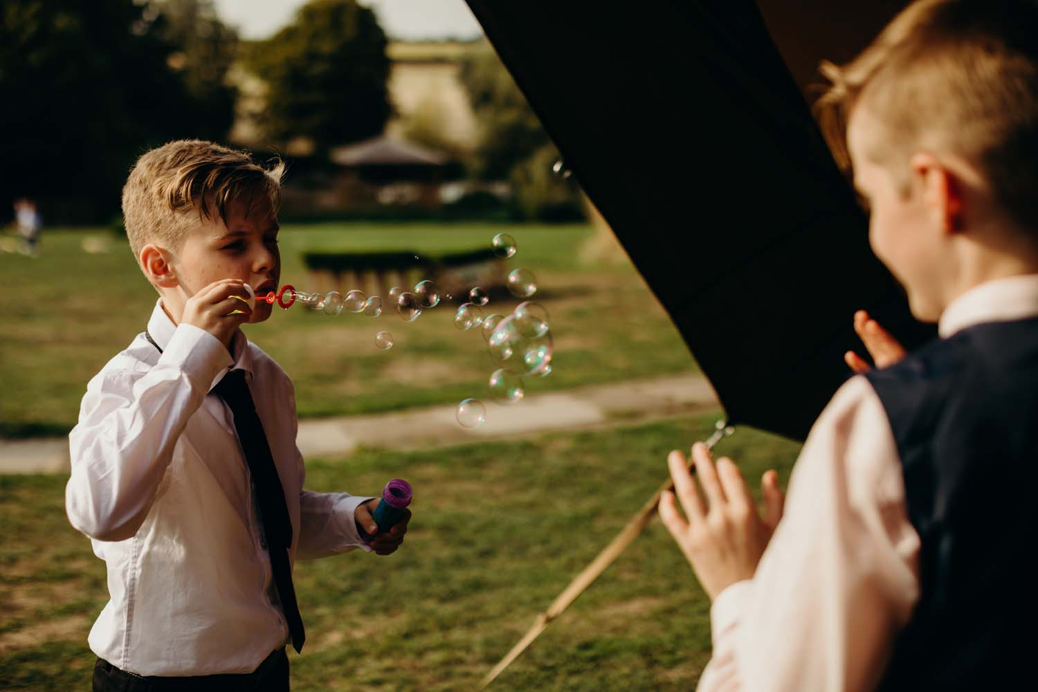 Boy blows bubbles at wedding