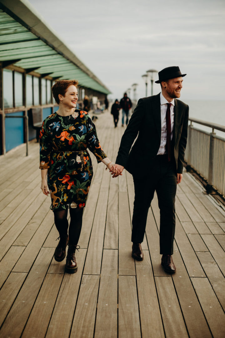 Newlyweds walking on Boscombe Pier, Dorset