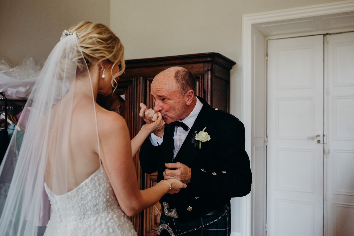 father of bride kisses his daughters hand