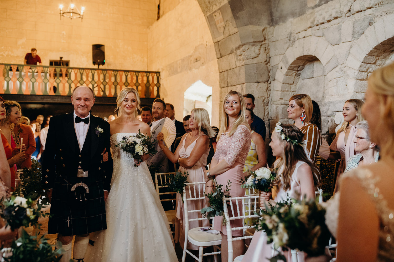 bride walks down aisle at chateau