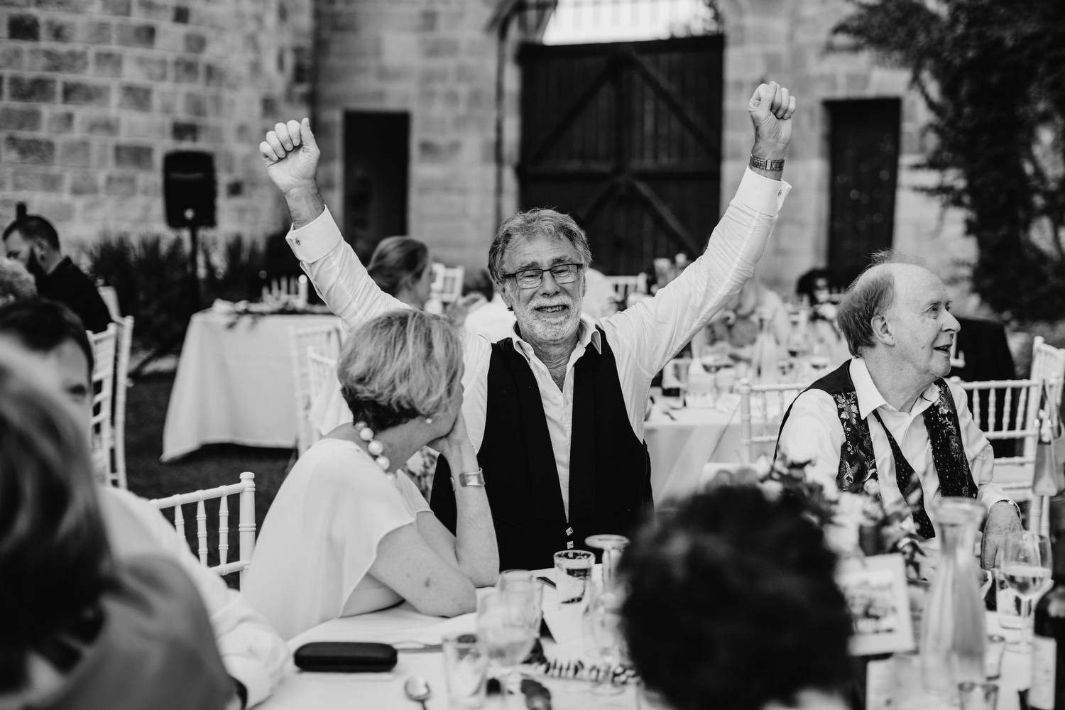 wedding guest puts hand up in air