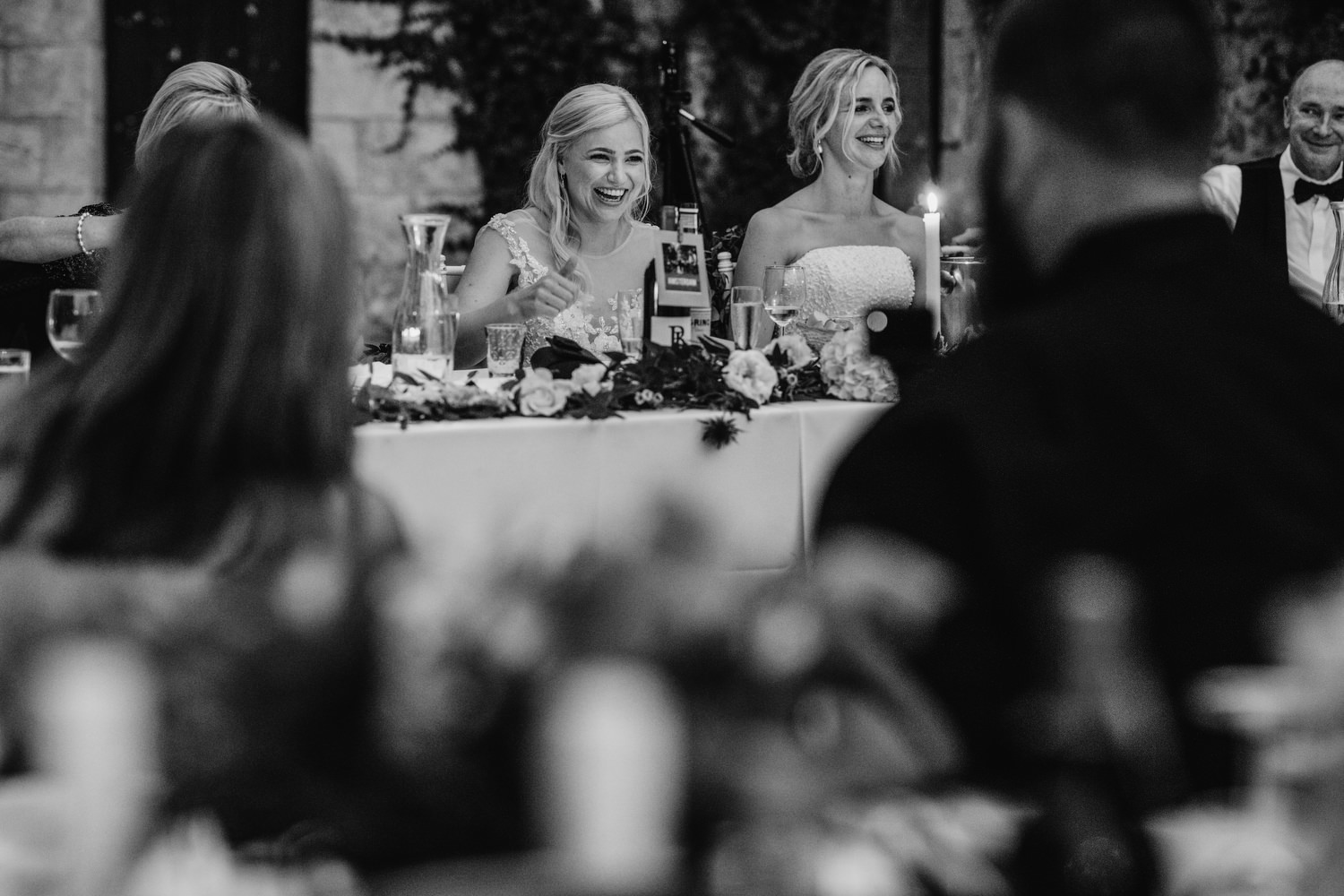 Both brides laughing during speech
