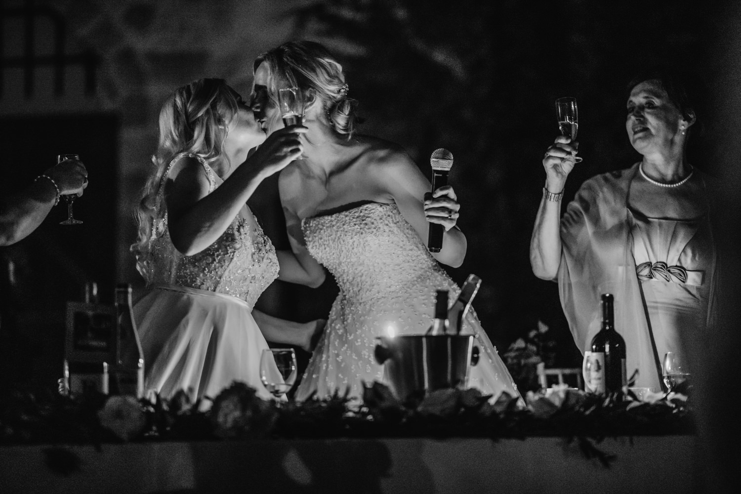 newly wedded brides kiss after speeches