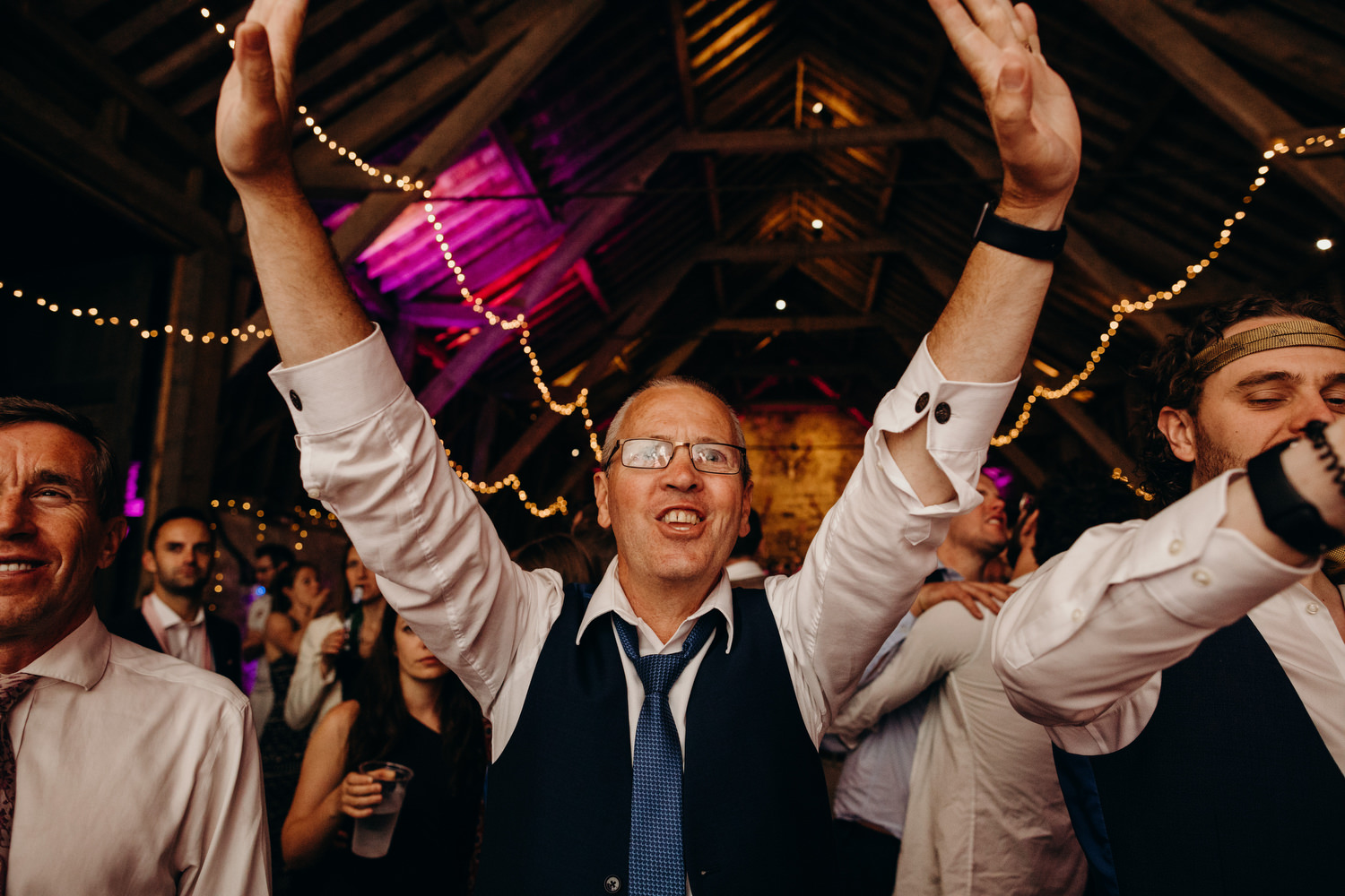 guy puts hands up in air at wedding