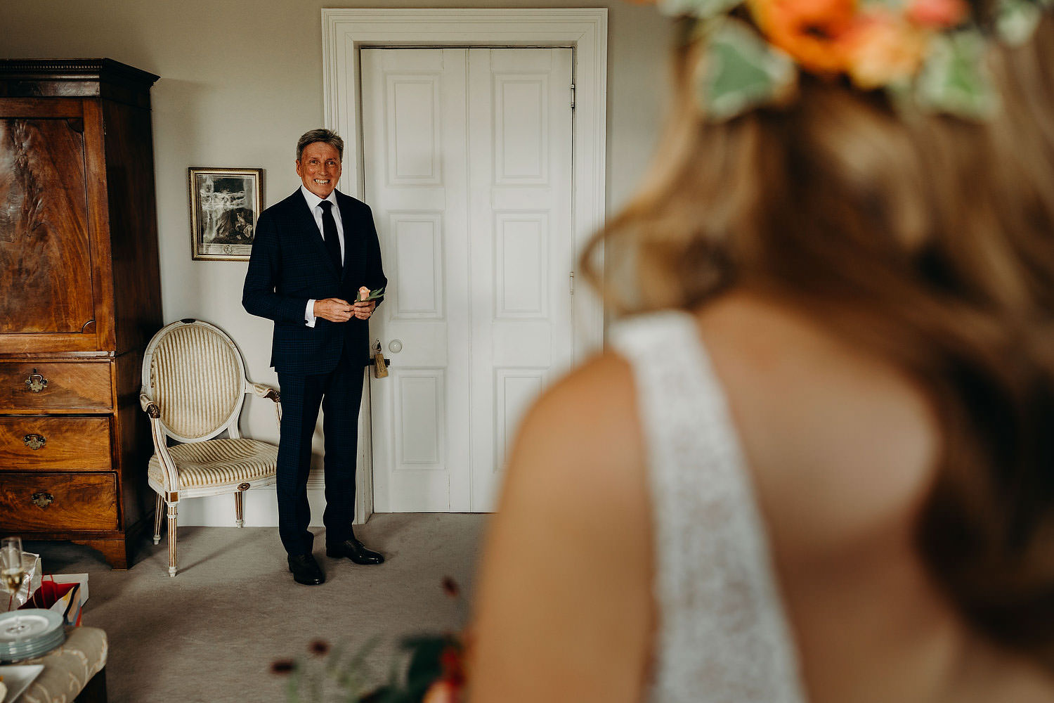 father looks at bride in dress