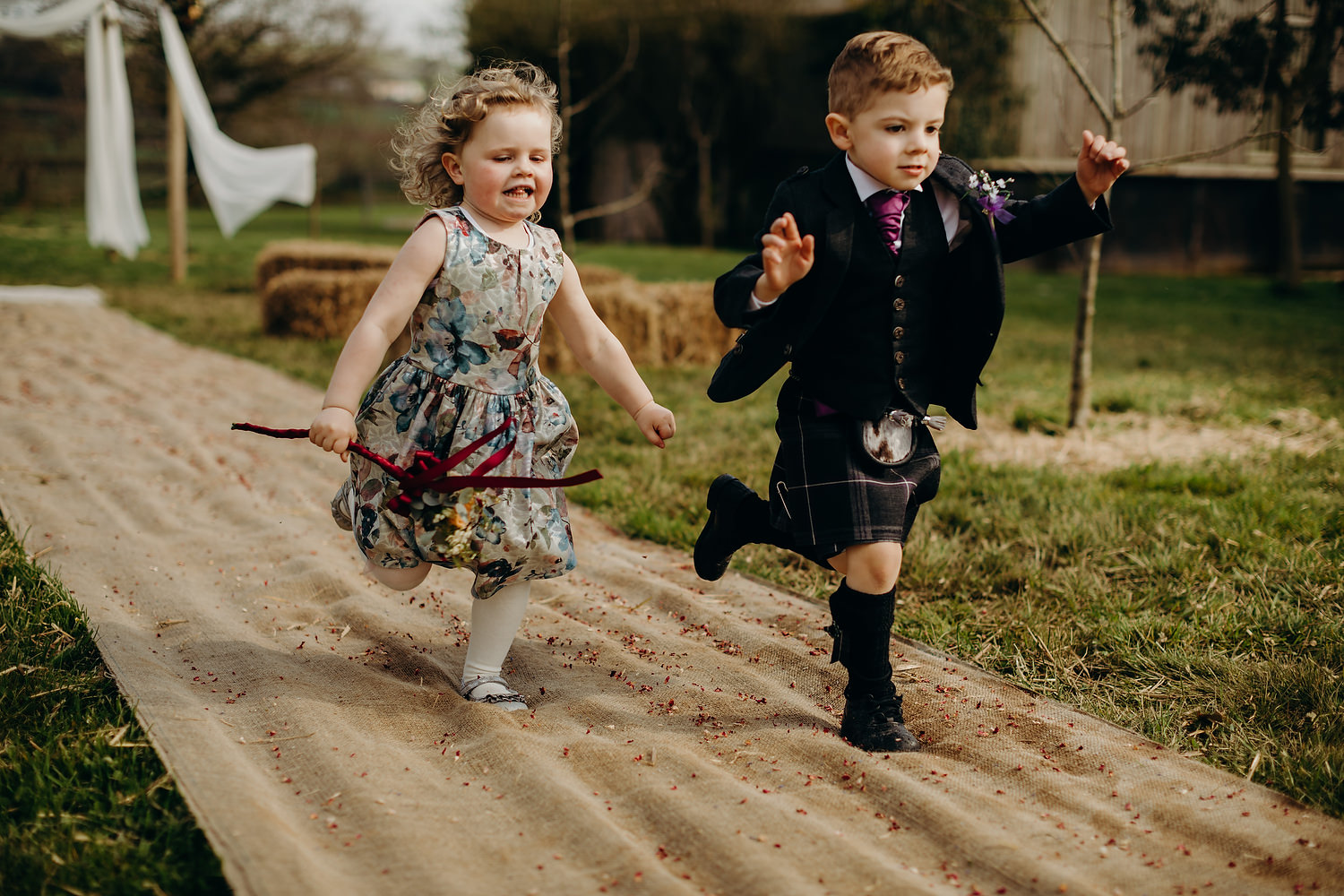 flower girl and page boy run down aisle