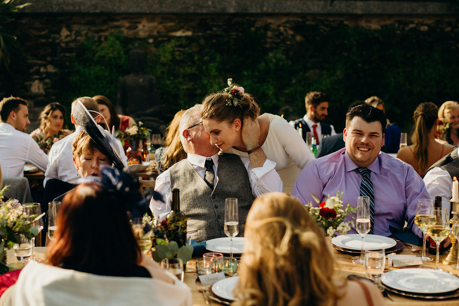 father of groom kisses bride