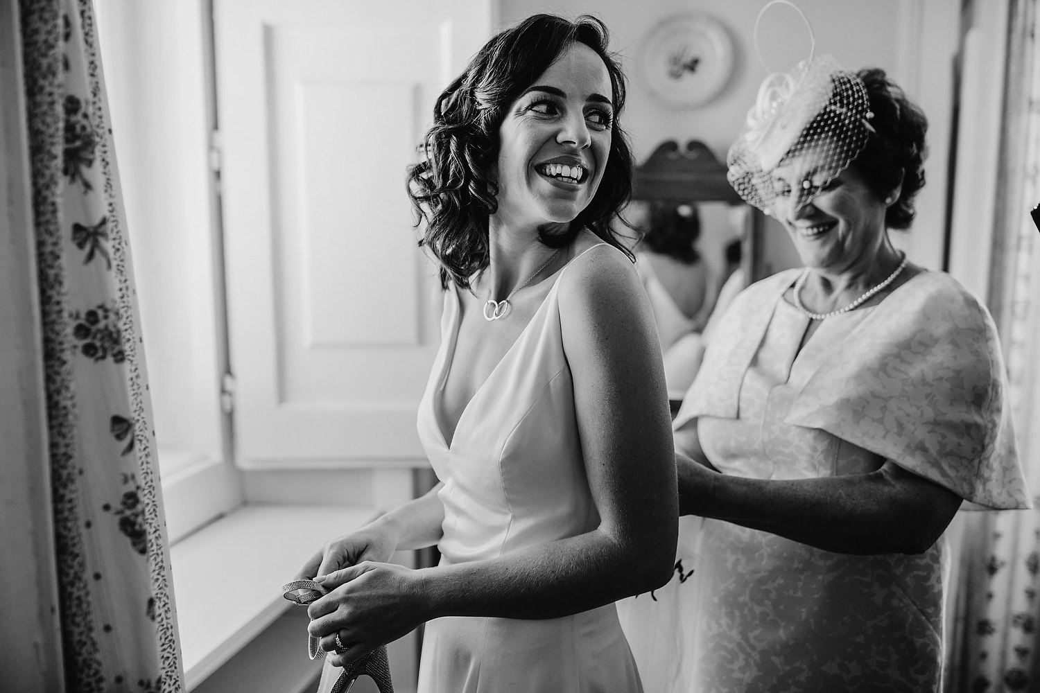 mother helps bride in dress