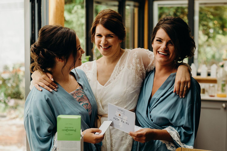 bride hugs bridesmaids on morning of wedding