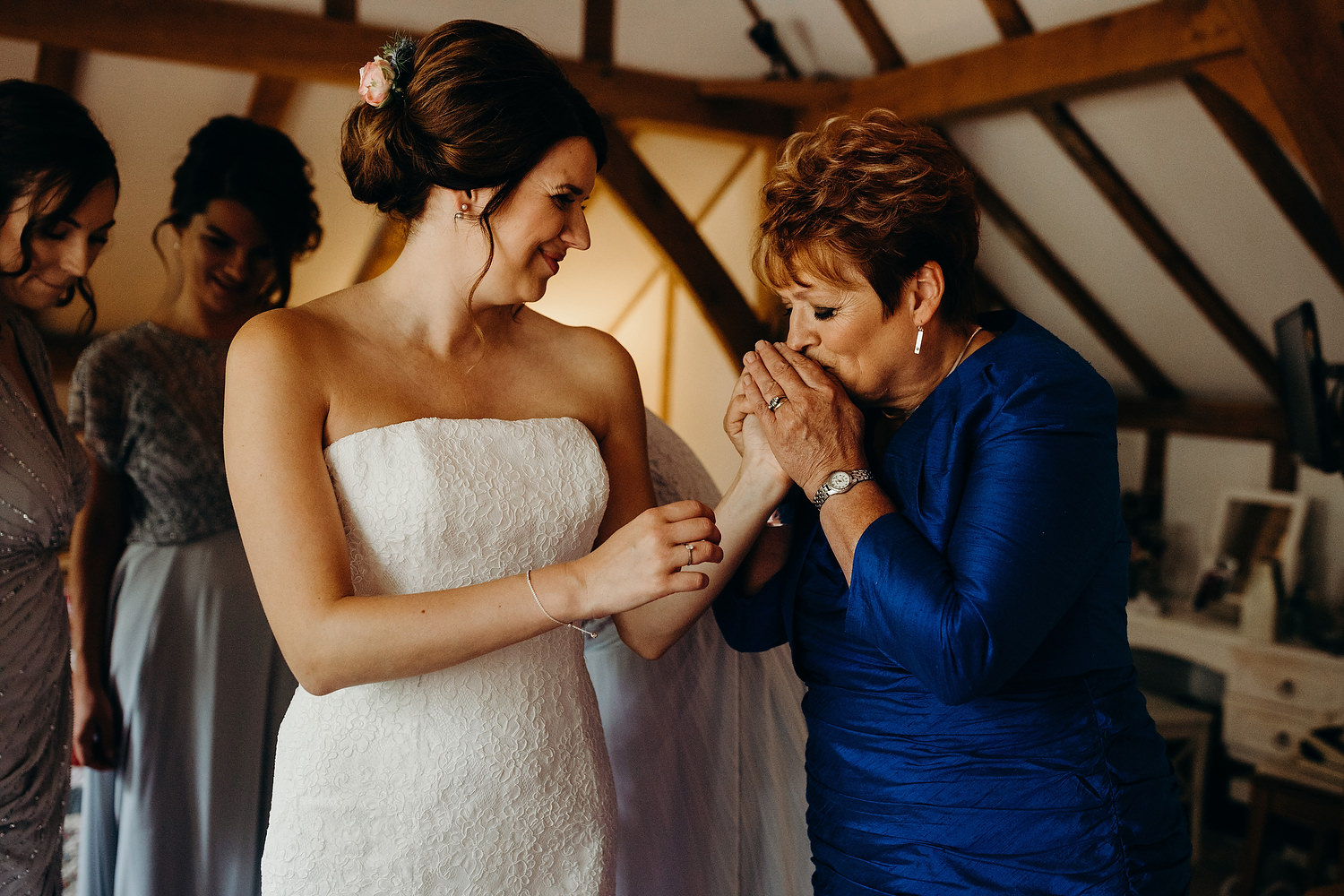 Brides mother kisses daughter on hand