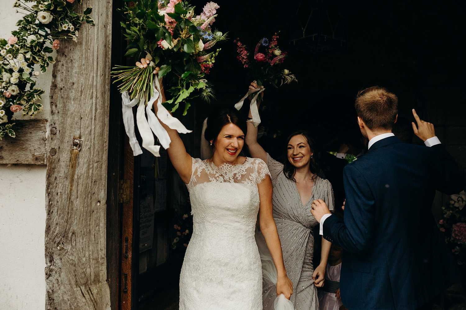 bride holds bouquet in air after ceremony