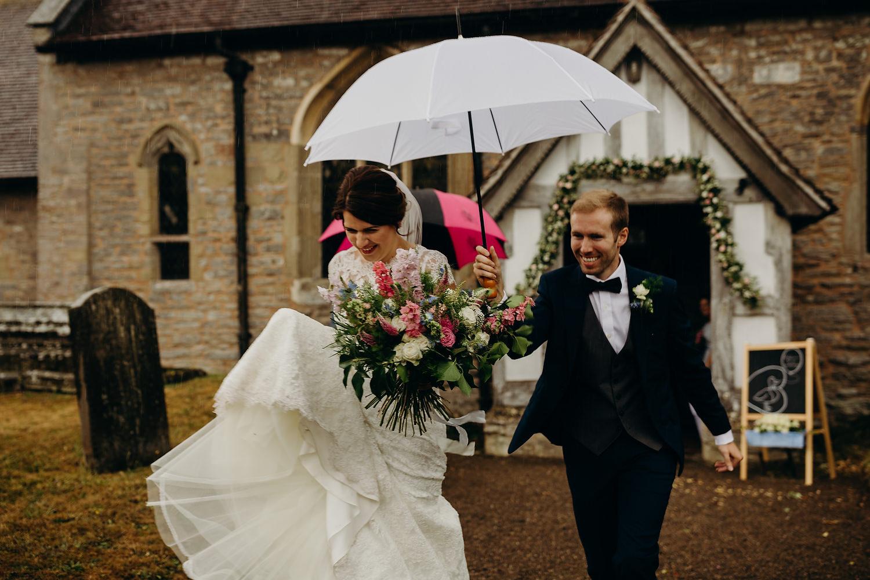 bride and groom run in the rain