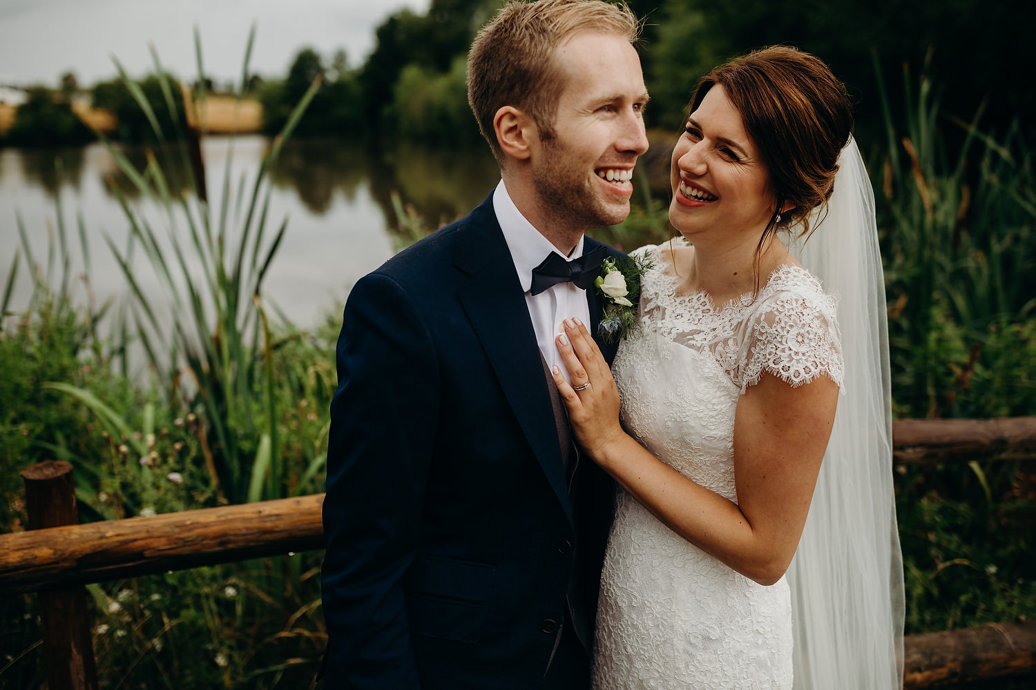 bride and groom smiling at millpond in Worcestershire