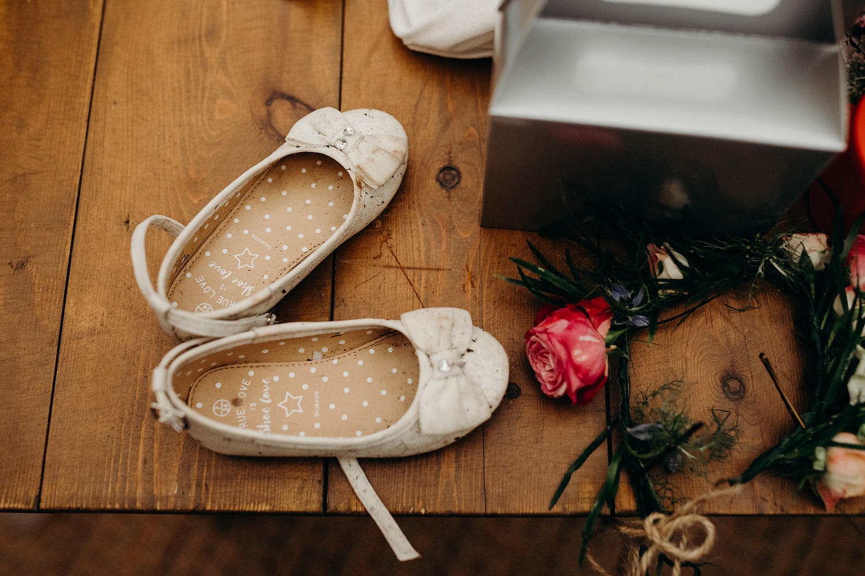 muddy flowergirl shoes at rainy wedding