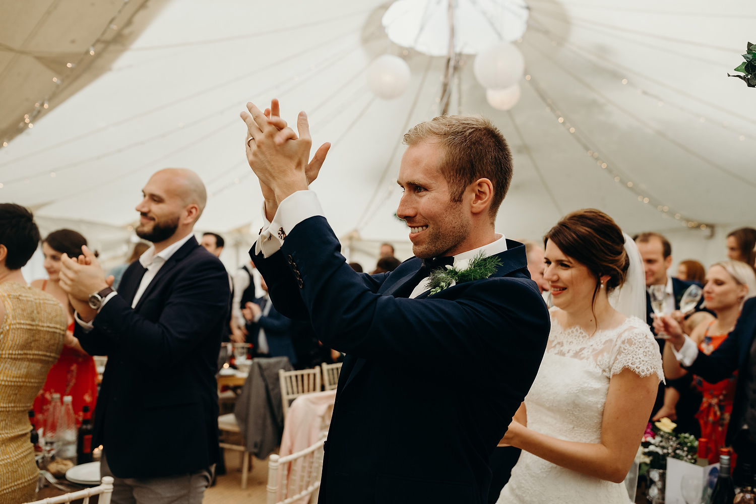 groom claps during speeches in marquee