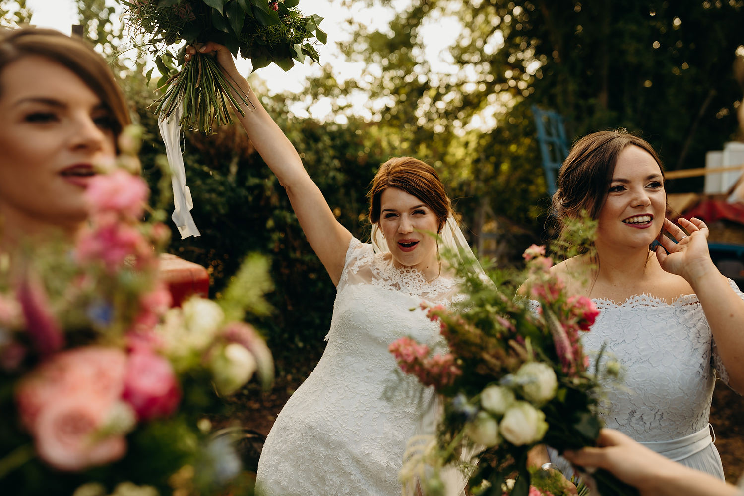 bride holds bouquet in the air