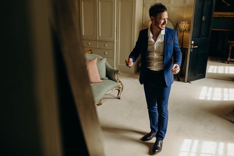 groom putting suit on