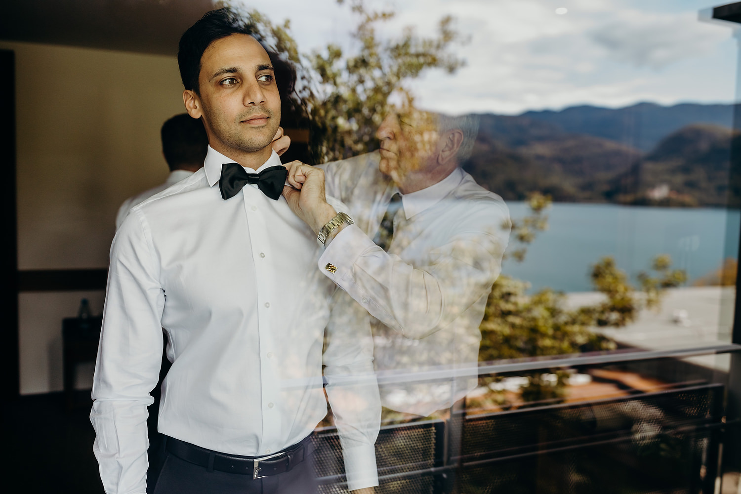 Best man gets bow tie on with lake in reflection
