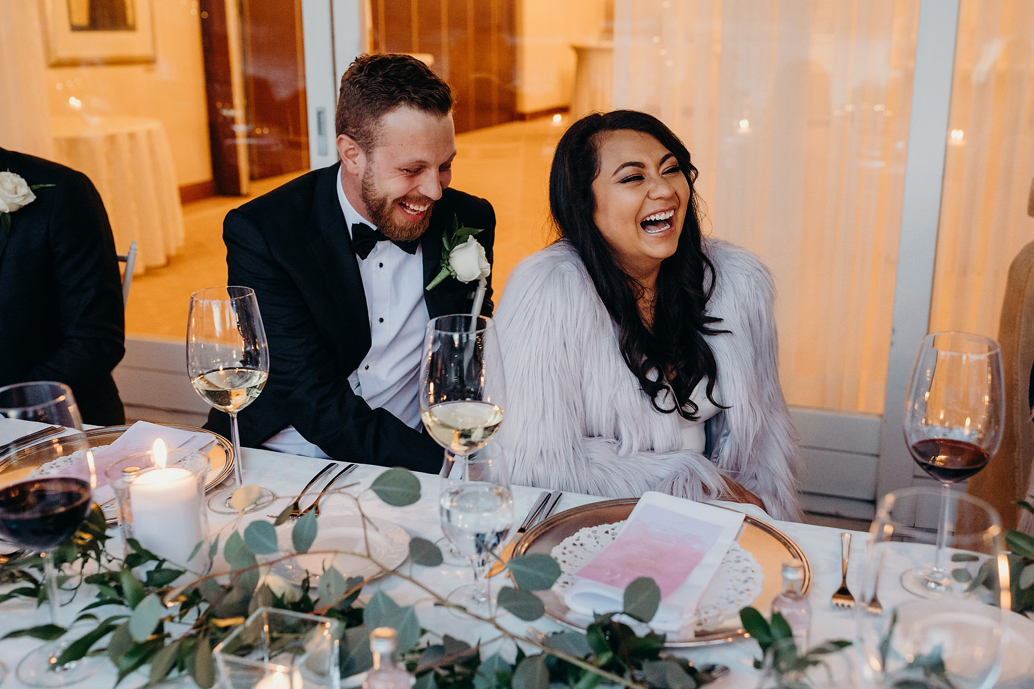 bride and groom laughing at wedding table