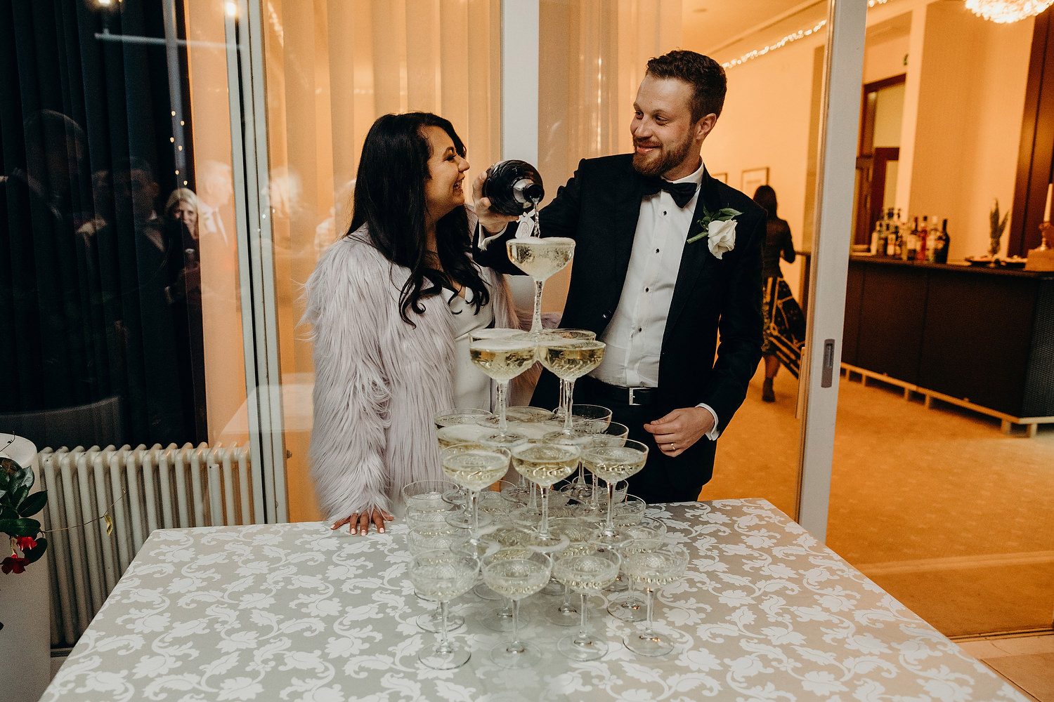 bride and groom fill champagne glasses