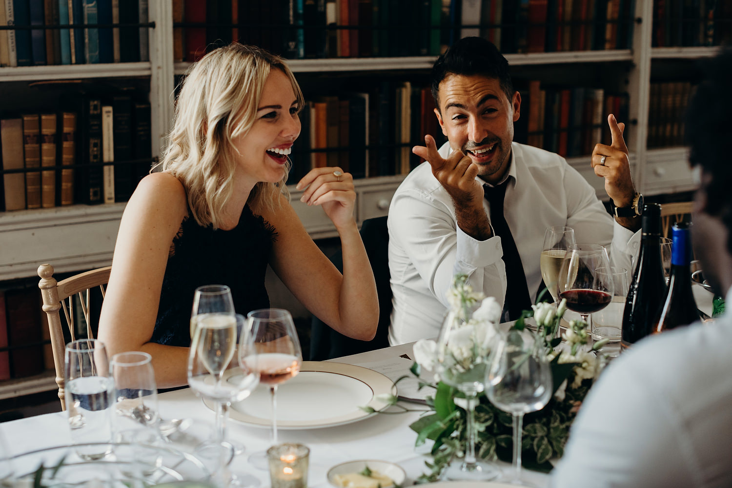 wedding guests laugh at table