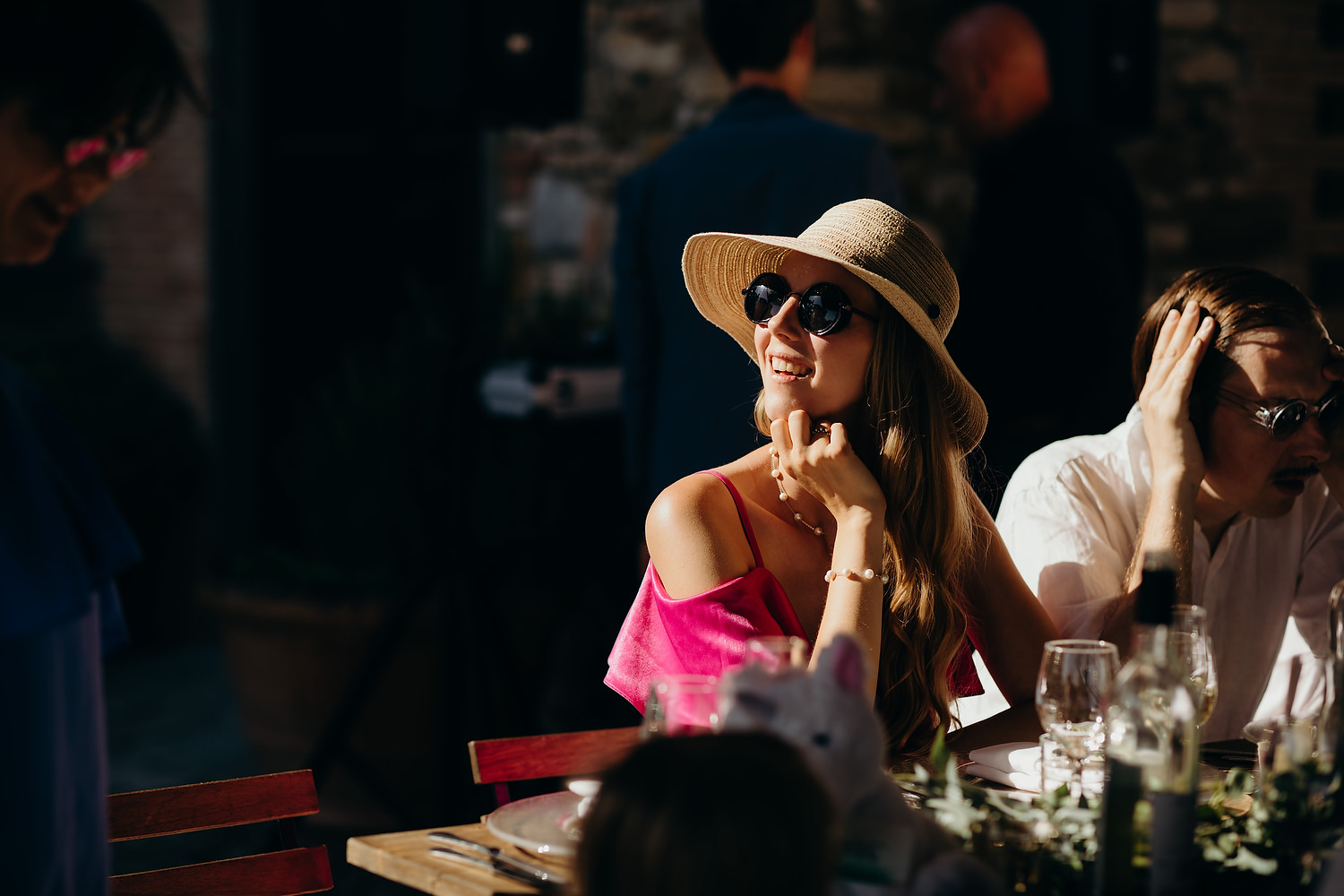woman with shades and hat at Tuscany wedding